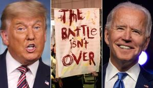 """Sign that reads, """"The Battle Isn't Over,"""" between a photo of President Trump and Resident Biden"""