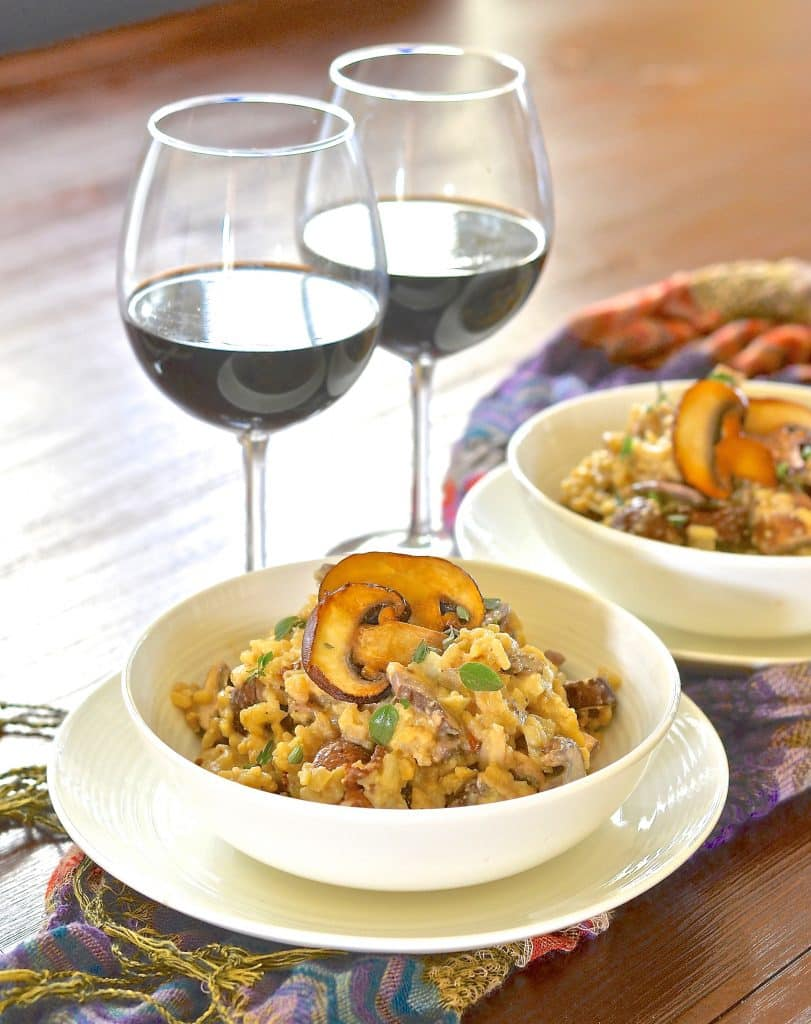 A bowl of vegan risotto with red wine in glasses