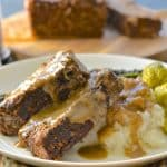 slices of vegan meatloaf drizzled in gravy, on a plate with mashed potato and brussels sprouts