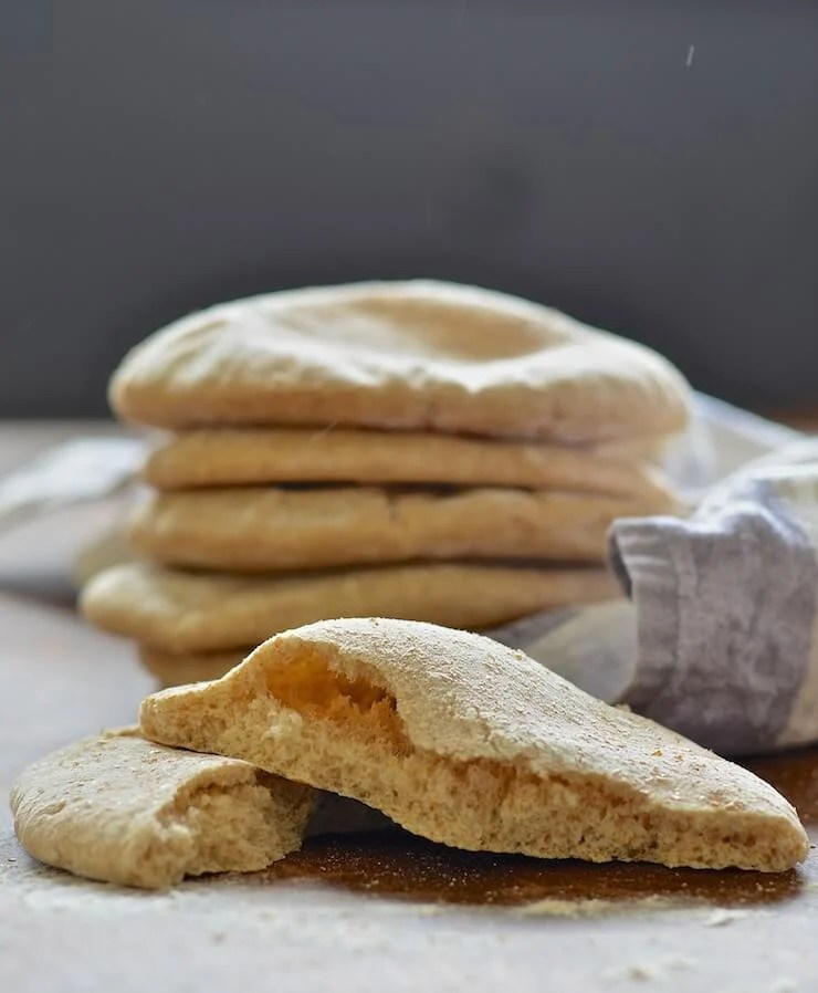 homemade pita-bread cut open with pile of uncut ones in the background