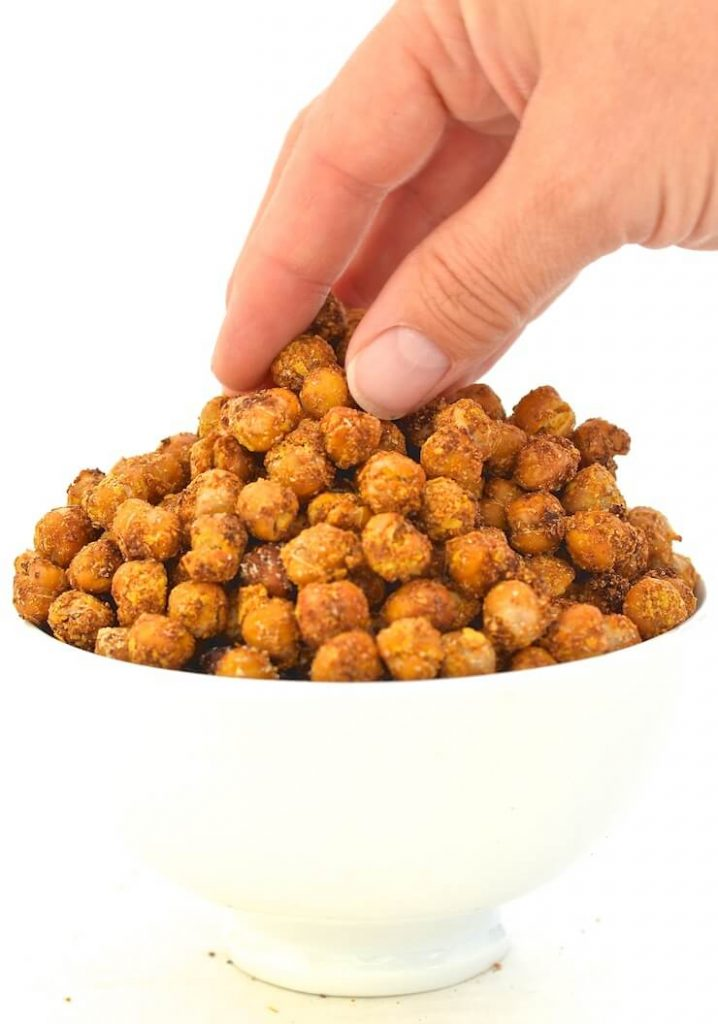cheese & onion crispy roasted chickpeas in a bowl with a hand taking some