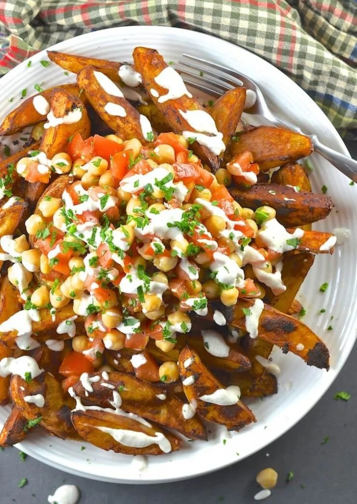 Loaded Taco Fries on a plate and drizzled in lime crema. Shot taken form above