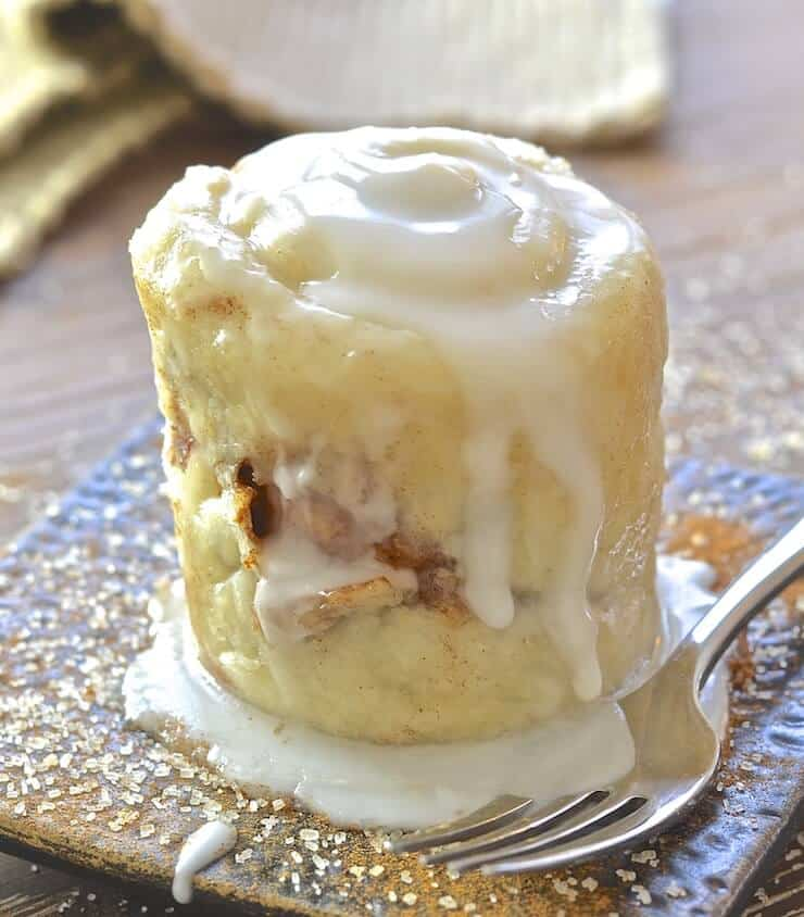 Cinnamon Roll in a Mug turned out and drizzled in frosting