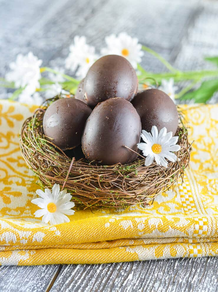 Homemade Vegan Creme Eggs nestled in a pretty little bird's nest with daisy's scattered around