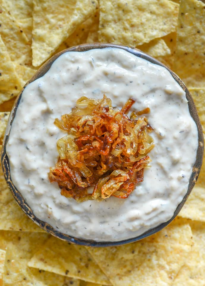 creamy onion garlic dip close up shot with caramelized onions on top