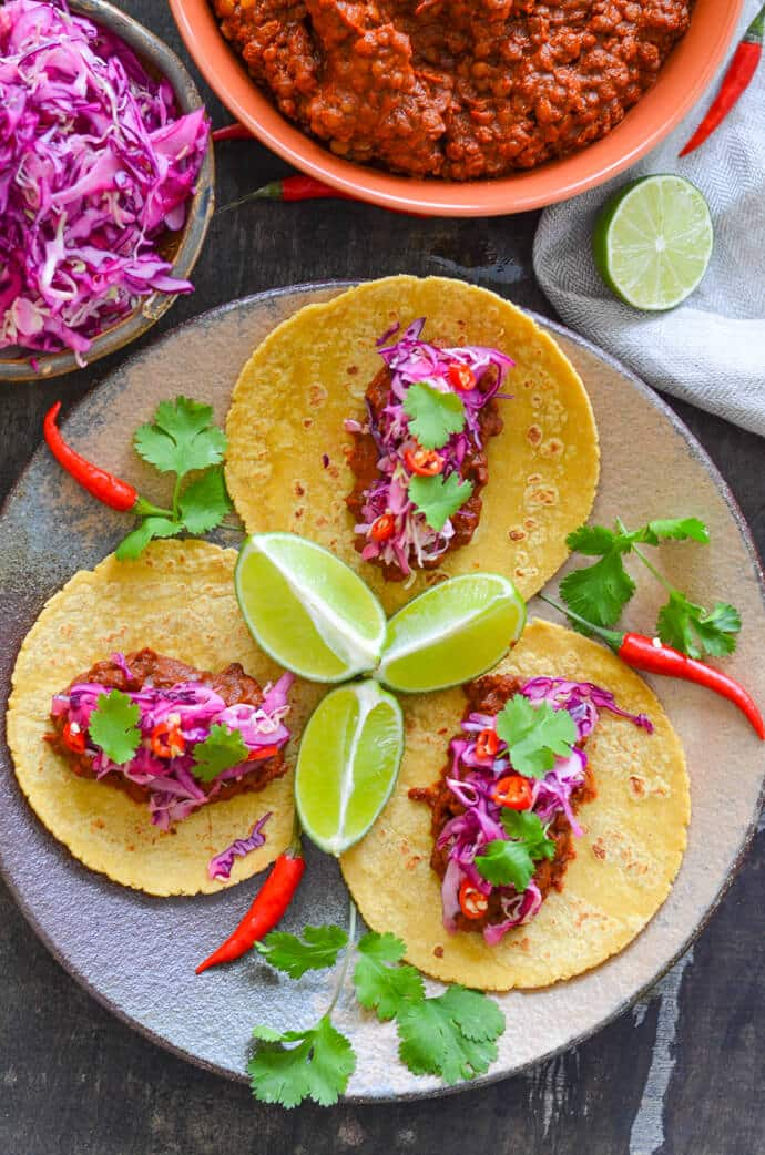 enchilada lentil tacos with lime slaw from above with sliced lime and chili garnish