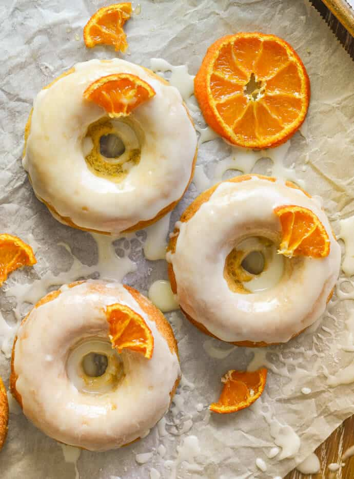 3 frosted, sticky, orange olive oil baked donuts with candied orange pieces