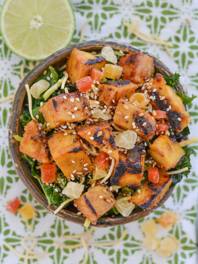 Overhead shot of Sticky Coconut Lime Pan-Fried Tofu in a bowl over a bed of salad, garnished with dried fruit