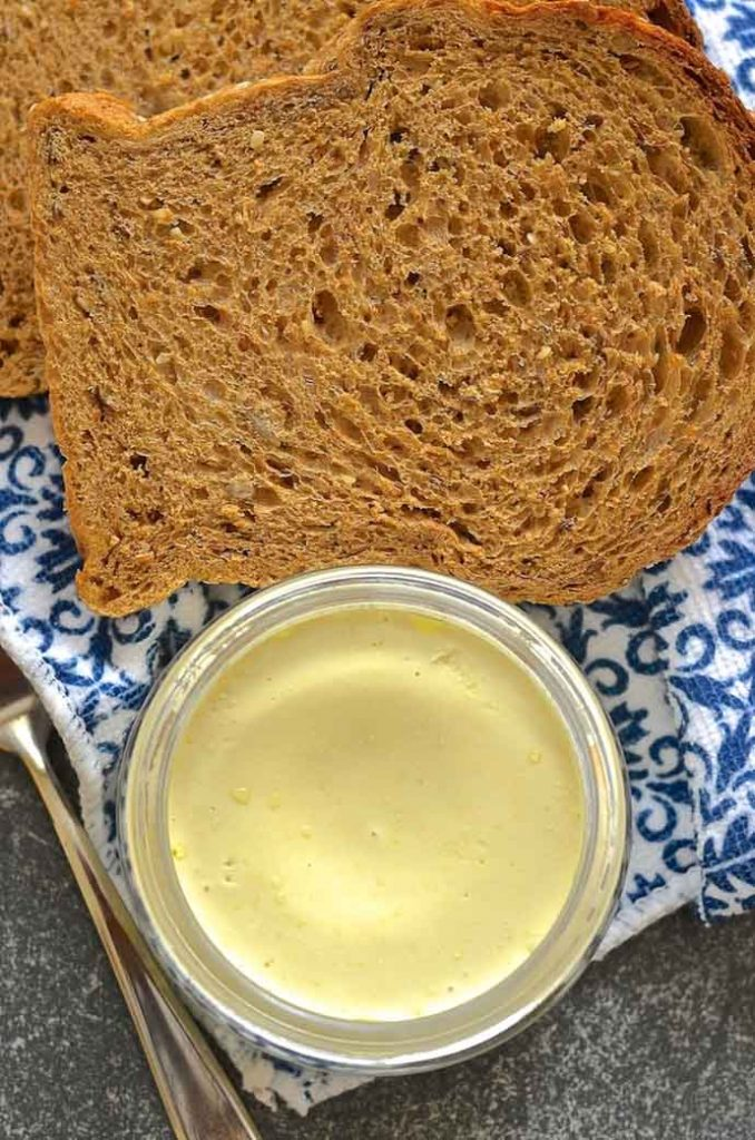 Smooth & creamy easy vegan butter in a jar with fresh bread on the side