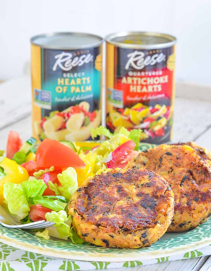 Thai Style Vegan Crab Cakes with salad and cans of hearts of palm and artichokes in background
