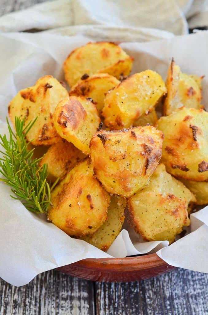 Healthy No Oil Crispy Roasted Potatoes in a bowl with rosemary garnish