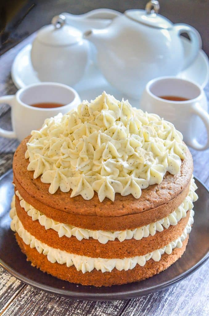 Layered Earl Grey Vegan Cake with Lemon Frosting in foreground with white tea set in background