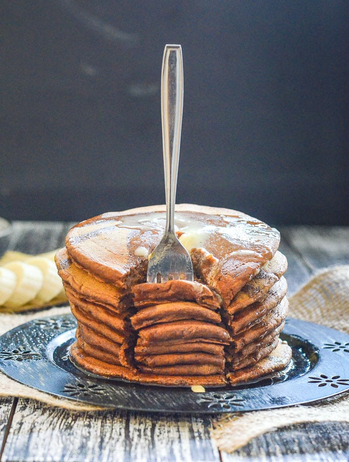 Vegan Gingerbread Pancakes with melty butter on top & fork stuck in ready to take a big chunk