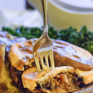 Close up shot of a slice of Easy Vegan Mushroom Pie with gravy.