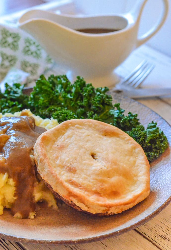 Individual Easy Vegan Mushroom Pie on a plate with mashed potato, kale & gravy