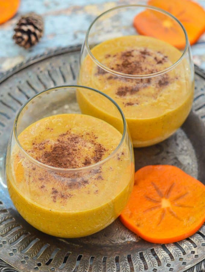 Cinnamon Persimmon Smoothie in glasses and sprinkled with cinnamon, on an old fashioned pewter tray