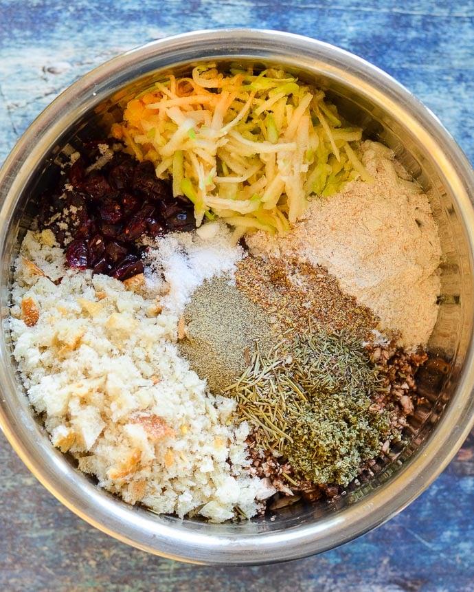 ingredients for Mushroom Lentil Loaf in a mixing bowl - red lentils, green lentils, onion, walnuts, mushrooms, bread crumbs, dried cranberries, grated apple, flax, herbs & seasoning