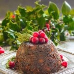 Vegan Christmas Pudding turned out onto metal plate and topped with frosty cranberries and fresh rosemary