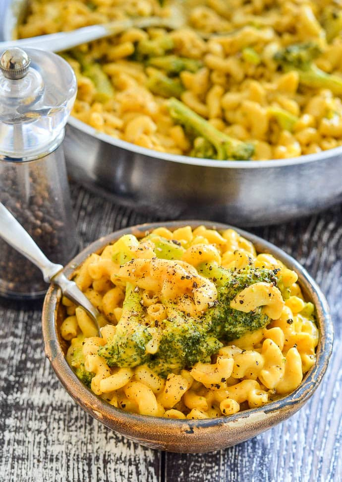 Dairy free mac and cheese with broccoli and black pepper in a small brown bowl, next to a pepper pot and with the pan full of mac and cheese in the background