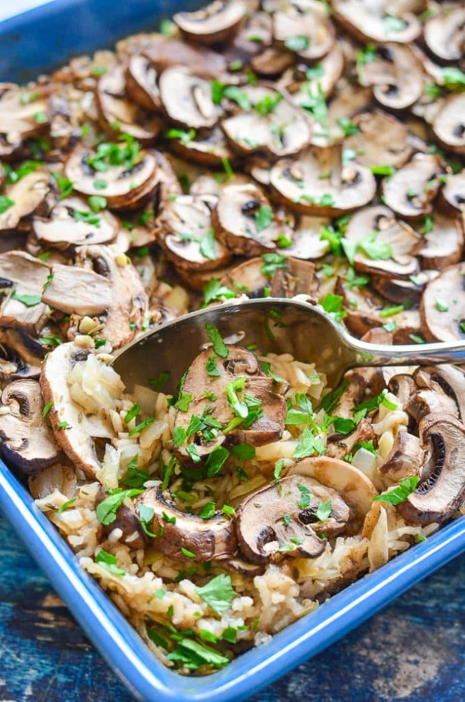 easy Oven Baked Garlic Mushroom Rice being served up with a spoon