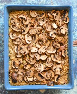Easy Oven Baked Garlic Mushroom Rice cooked in a blue dish