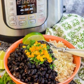 Instant Pot Black Beans in a bowl over rice with the Instant Pot in the background