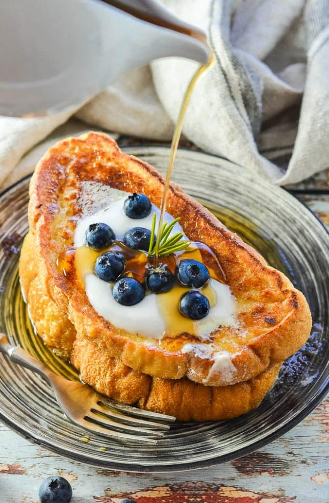Vegan French toast topped with yogurt and blueberries. A stream of golden maple syrup is being poured all over it.