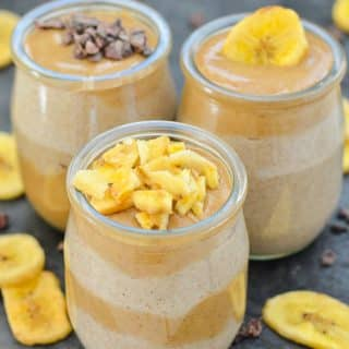 three small jars of chia seed pudding topped with caramel, chopped dried banana and cacao nibs