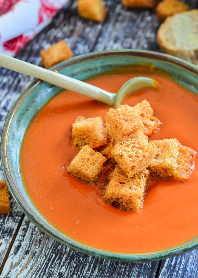 A bowl of tomato soup with croutons and a cute green ceramic spoon