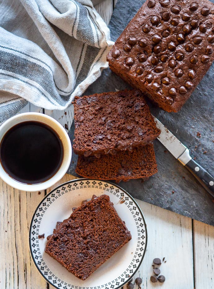vegan chocolate banana bread slices on a board, one slice on a plate next to a mug of coffee