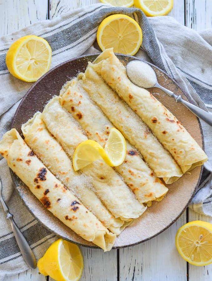Vegan English Pancakes rolled on a plate and topped with sugar and lemon