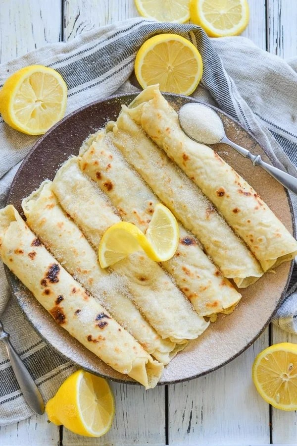 Foolproof Vegan English Pancakes. Quick & easy to make & great for dessert or brunch! They are beautifully freckled and so good straight from the pan, served glistening with fresh lemon juice & sugar.