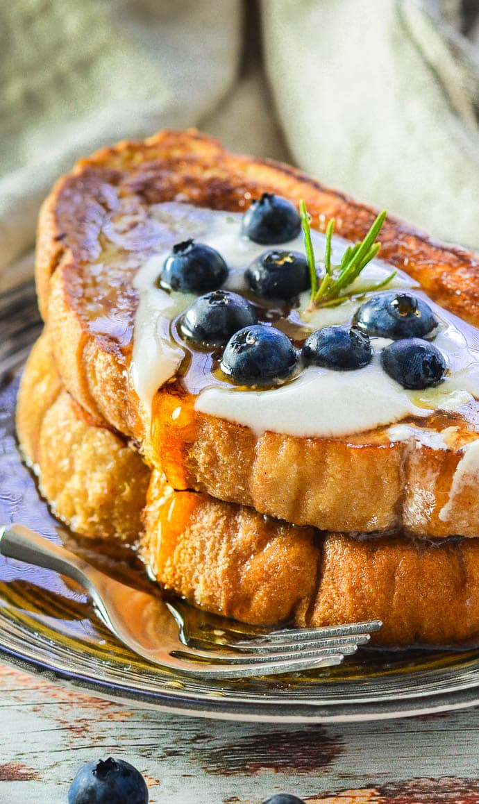 Close up shot of Vegan French Toast with a dollop of yogurt, blueberries and a drizzle of golden maple syrup running down the side