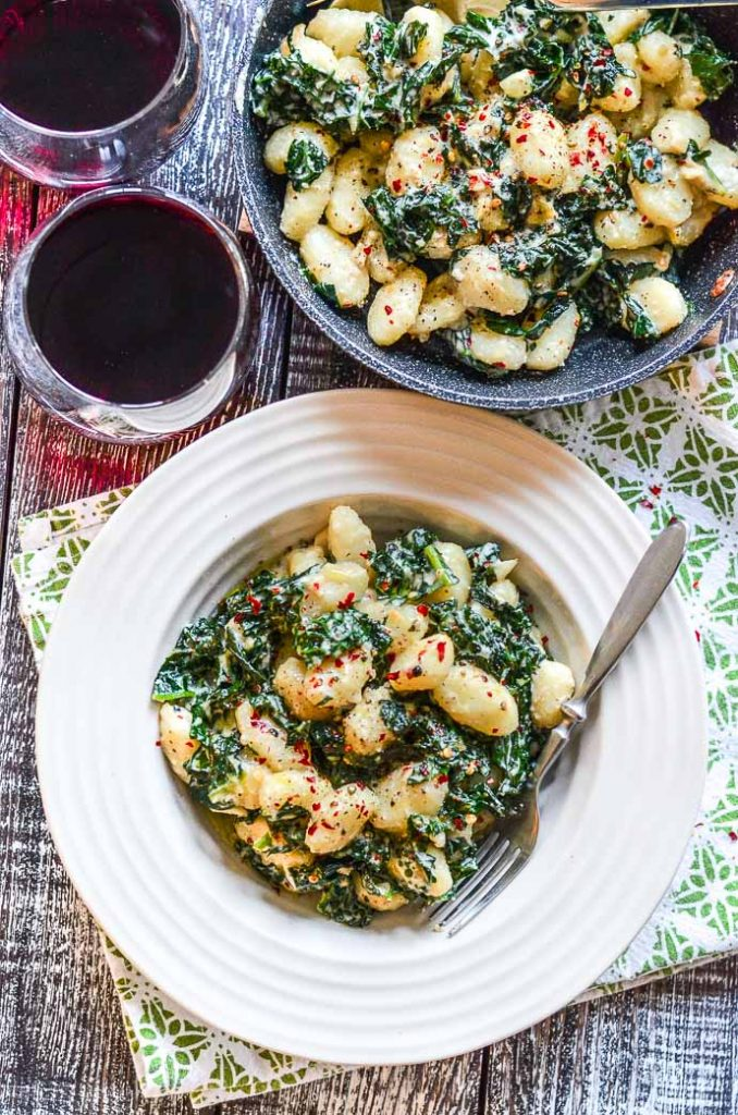 Vegan Gnocchi in a bowl with 2 glasses of wine and the pan the gnocchi was cooked in, all take from above