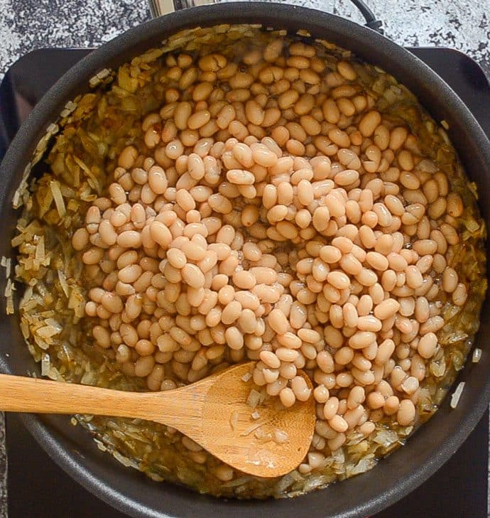 onions and navy beans in a skillet ready to make BBQ Baked Beans
