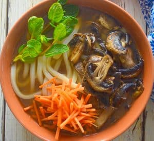udon noodle soup topped with carrot, mushrooms and mint