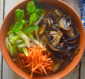udon noodle soup topped with carrot, mushrooms, mint & green onions