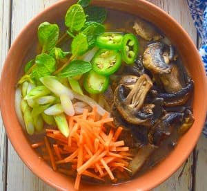 udon noodle soup topped with carrot, mushrooms, mint, green onions and jalapeños