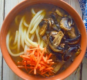 udon noodle soup topped with carrot and mushrooms