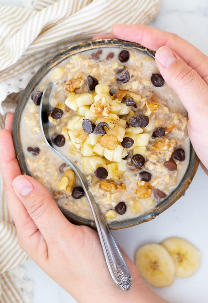 Hands holding a bowl of Overnight Oats topped with banana, nuts and chocolate