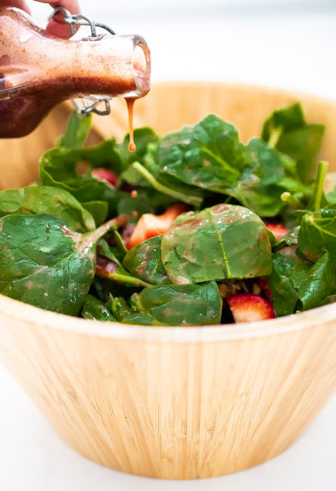 oil-free strawberry vinaigrette pouring on a Strawberry Spinach Salad