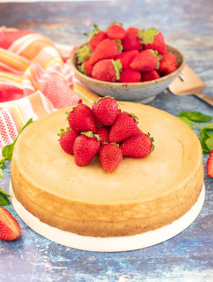 The best Vegan New York Cheesecake topped with fresh strawberries