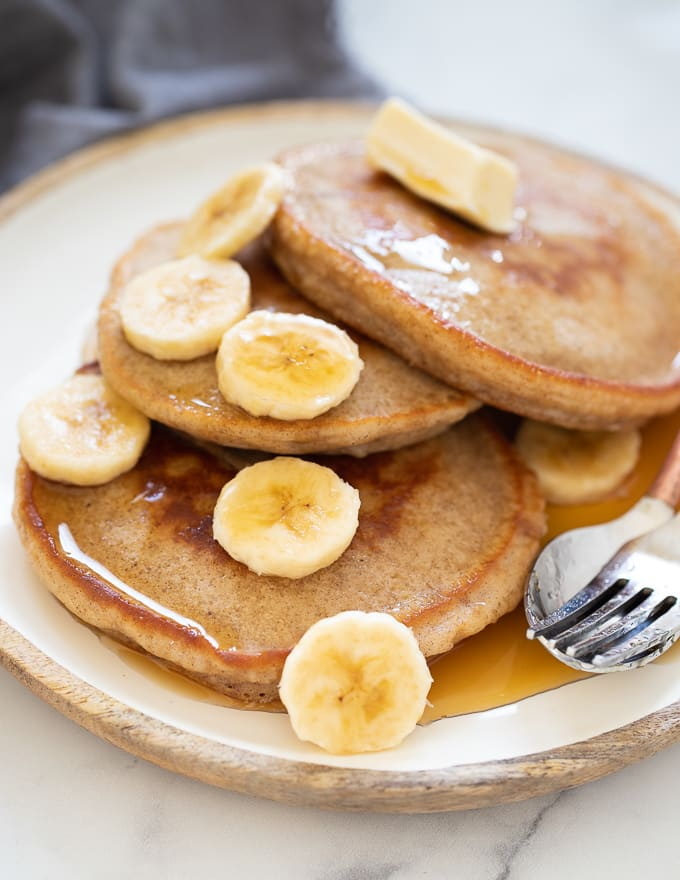 Vegan Banana Pancakes served up on a plate with maple syrup and banana