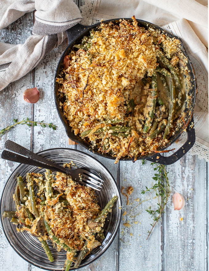 Vegan green Bean casserole in a skillet with a portion served on a plate