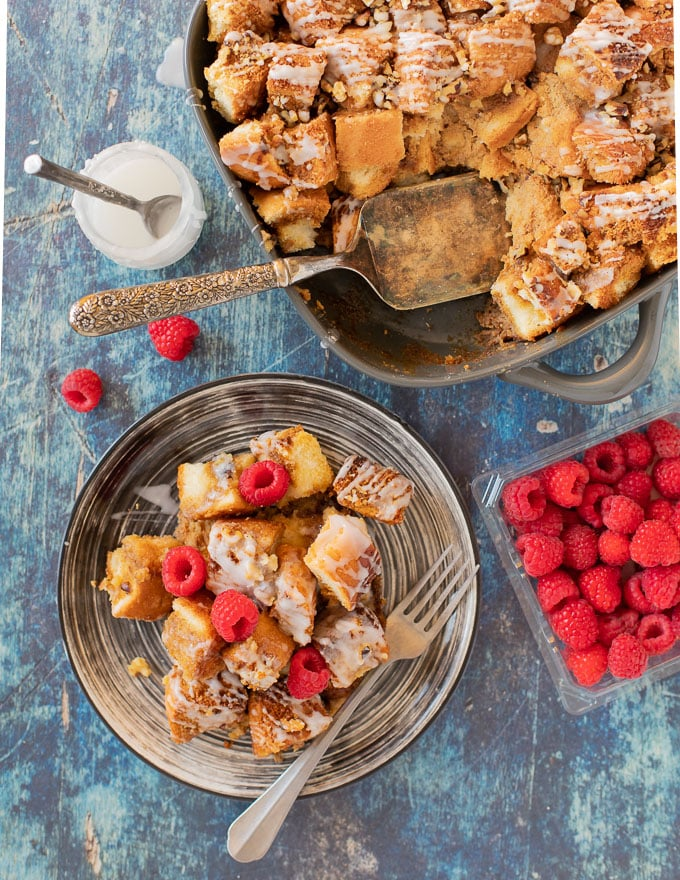 Vegan French Toast Casserole from above with a portion on a plate and a scattering of raspberries