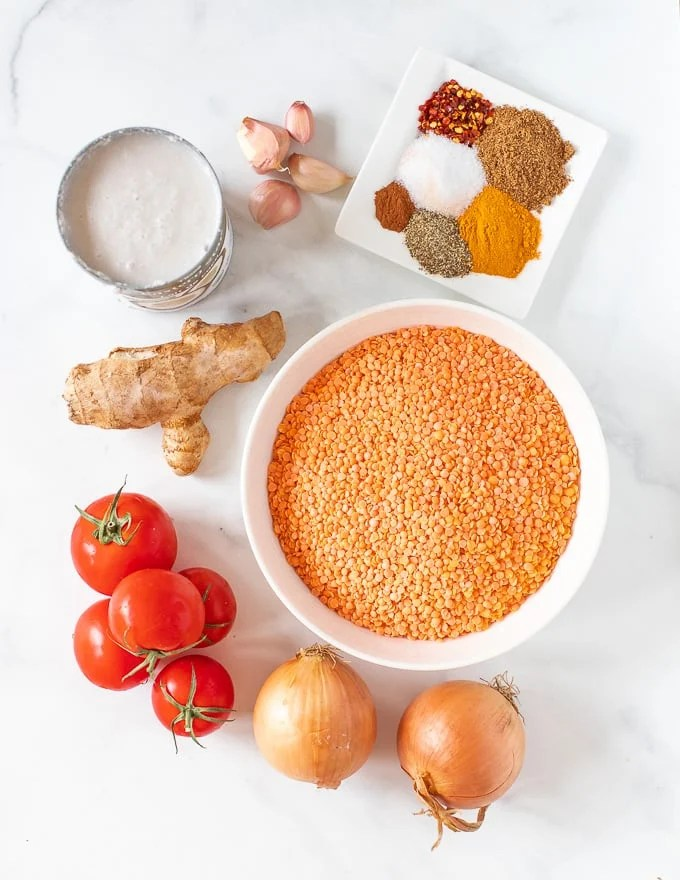 The ingredients for Instant Pot Lentil Dal laid out on a white marble surface