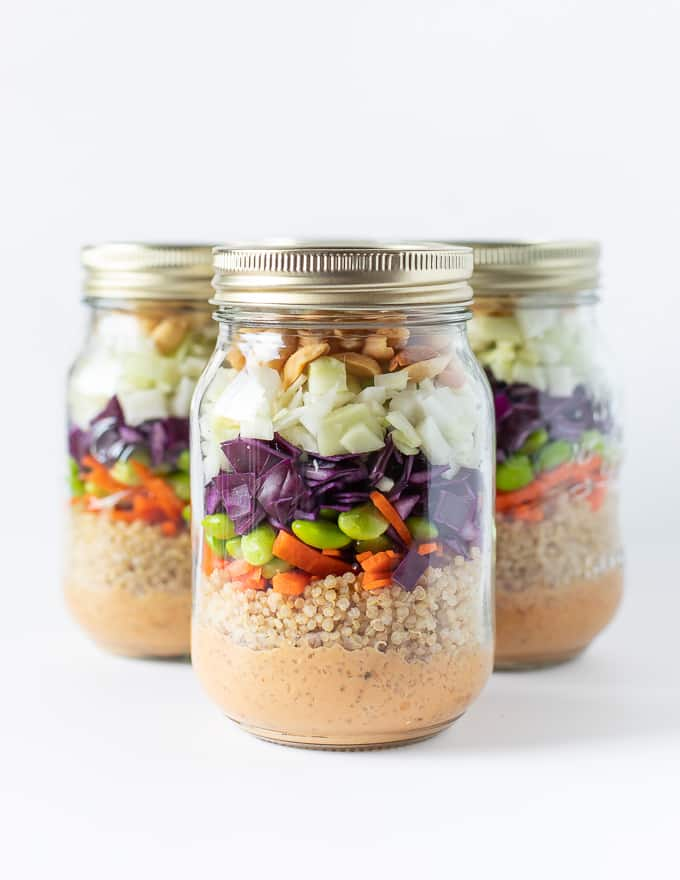 A layered salad in a mason jar. Dressing in bottom then quinoa, carrots, purple cabbage, green cabbage, edamame beans, peanuts all piled on top