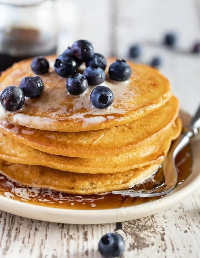 A stack of Vegan Gluten Free Pancakes with fresh blueberries