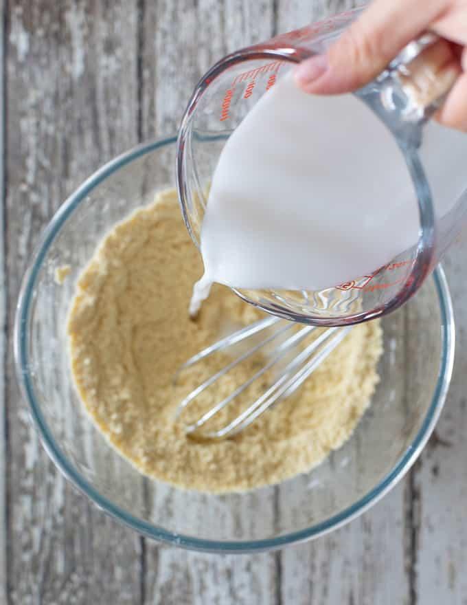 Vegan milk pouring into dry ingredients for Vegan Gluten Free Pancakes