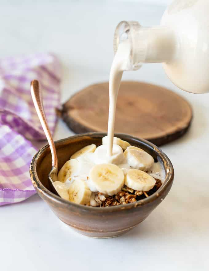Cashew Milk being poured on granola and sliced banana